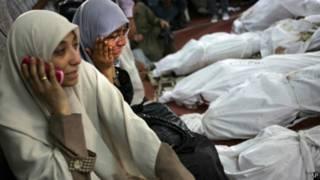 Mulheres ao lado de corpos das vítimas. Crédito: AP