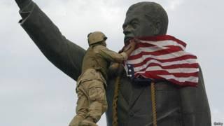 Soldado estadounidense pone bandera sobre la cabeza de la estatua de Sadam Hussein en Irak