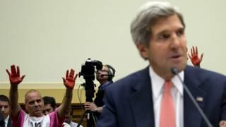 Palmas rojas tras el secretario de Estado John Kerry, durante su comparecencia en el COngreso para explicar el caso de Siria