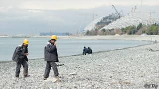 Рабочие возле недостроенного олимпийского объекта