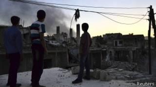 Crianças observam fumaça de suposto tanque do governo destruído por rebeldes