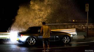 香港島維多利亞港海旁一名男子在巨浪刷岸下試圖返回他的汽車(22/9/2013)