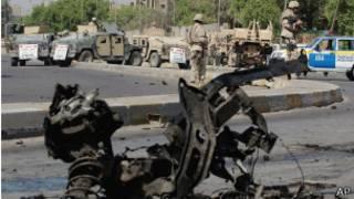 Мужчина смотрит на поврежденные автомобили после взрывов в Багдаде