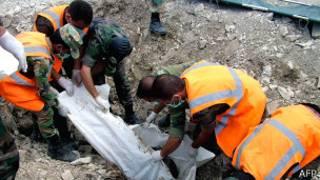 Из массового захоронения под Латакией извлекают тело (фото распространено официальным агентством САНА 20 августа)
