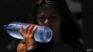 Mulher com garrfa de água em Sevilha (foto: AFP)
