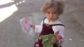 دختر بچه سوری با مقداری سبزی در دستانش