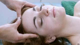 Mujer haciéndose un masaje en la cabeza