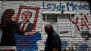 Homem passa ao lado de pichação em apoio ao governo argentino (foto: AP)