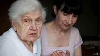 una señora mayor es acompañada de la mano por otra más joven