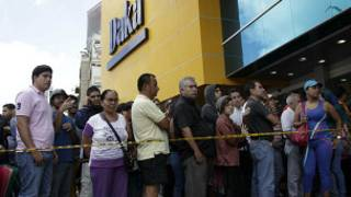 Clientes faxem fila ao lado de loja da rede Daka (foto: AP)