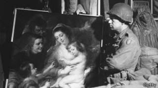 Американский солдат смотрит на бесценное полотно, найденное в мае 1945 года в Германии