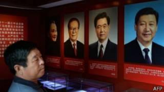 Житель Китая смотрит на портреты руководителей КПК