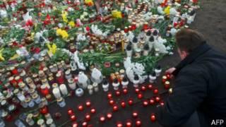 Мужчина зажигает свечу во время минуты молчания на месте трагедии в Латвии