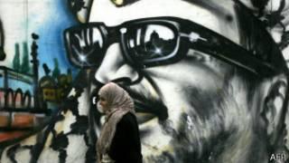 Une femme passant devant un graffiti représentant Yasser Arafat dans un camp de palestinien à Ain el-Heweh au Liban.