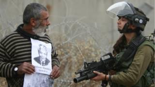 Palestino segura fotos de Mandela e Arafat durante protesto na Cisjordânia (foto: AP)