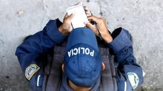 Oficial de policía en América Latina realizando anotaciones en una pequeña libreta