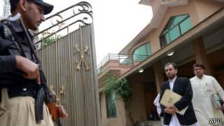 المحامي سميع الله أفريدي (في الوسط)، الذي يترافع عن الطبيب شاكل أفريدي، يخرج من المبنى بعد جلسة محكمة في 20 أكتوبر 2013.