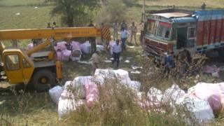 दुर्घटनाग्रस्त ट्रक के चारों ओर बिखरा हुआ सामान