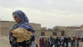mulher carrega pilha de pão | Reuters