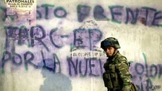 Un soldado colombiano pasa feente a un mural en apoyo a las FARC