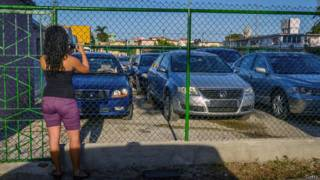 Mujer cubana fotografiando autos nuevos