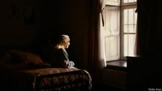 Anciana sentada en una cama mirando a la ventana
