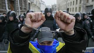 Un manifestante con las manos esposadas