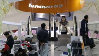 people stand under asign of Lenovo company
