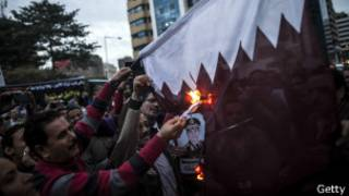 Supporters of Egypt's military chief Abdel Fattah al-Sisi set fire to a Qatari national flag during a demonstration outside the Qatari embassy in Cairo on November 30