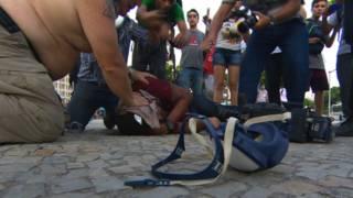 Cinegrafista da Rede Bandeirantes é socorrido após ser atingido por bomba (foto: BBC