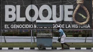 Vendedor passa em frente a propaganda contra o embargo americano a Cuba (foto: AP)