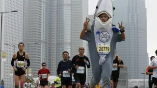 一名身穿反對魚翅服飾的香港馬拉松參賽者別上藍絲帶比賽(16/2/2014)