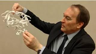 بيتر كوفني يمسك مجسم للبروتين والعقار الذي يوقف نشاطه