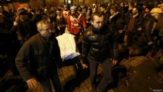Opositores do governo transportam corpo de manifestante morto na Ucrânia (foto: Reuters)