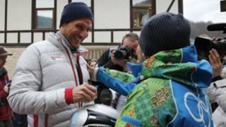 Волонтер фотографируется со спортсменом из Норвегии