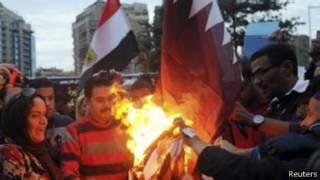 مصريون يحرقون علم قطر خارج سفارتها بالقاهرة