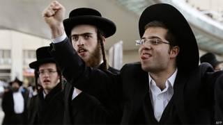 Jovens ortodoxos gesticulam contra policiais isralenses durante protesto em Jerusalém (AFP/Getty)