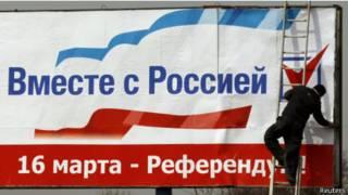 Рабочий вывешивает плакат (Симферополь, 12 марта 2014 г.)