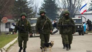 Militares supostamente russos caminham perto de base ucraniana (foto: Reuters)