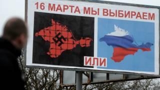 Cartaz na Crimeia mostra mapas da região pintado com a suástica nazista ou com cores russas, e dizeres: 'Escolheremos no dia 16' (Getty)