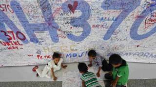 Crianças escrevem mensagens de apoio a passageiros e tripulantes de voo desaparecido MH3700, da Malaysia Airlines, no Aeroporto Internacional de Kuala Lumpur (Reuters)