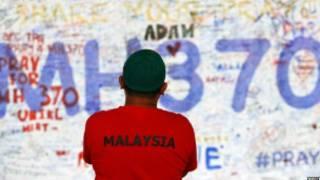 Pessoa observa mensagem de apoio a passageiros e tripulantes de voo desaparecido MH3700, da Malaysia Airlines, no Aeroporto Internacional de Kuala Lumpur (Reuters)