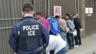 Oficial de migración de EE.UU. con deportados en la valla