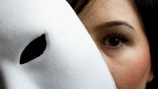 امرأة تضع قناعا مسرحيا أبيض أمام وجهها