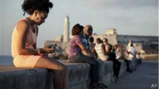 Una cubana mira el movil en el malecón