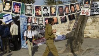 Израильский солдат идет мимо плакатов с изображением жертв палестинских заключенных