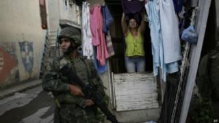 soldado em frente à casa de uma moradora da Maré   AP