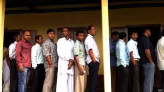 असम के डिब्रूगढ़ के एक केंद्र पर मतदान के लिए आए मतदाता