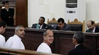 صحفيو الجزيرة الثلاثة يبتسمون اثناء وجودهم في قاعة المحكمة