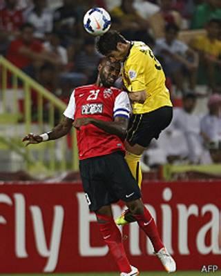 Dos futbolistas intentan cabecear el balón